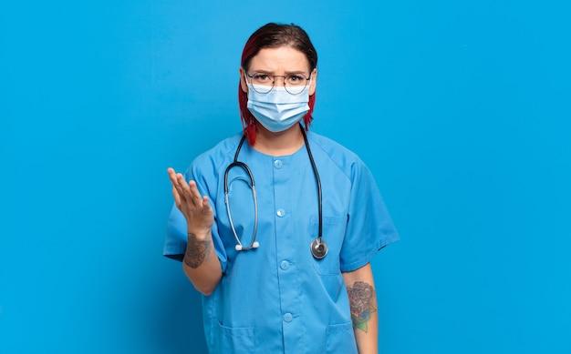 Młoda atrakcyjna kobieta z czerwonymi włosami czuje się szczęśliwa, zdziwiona i wesoła, uśmiecha się pozytywnie, realizuje rozwiązanie lub pomysł. koncepcja pielęgniarki szpitalnej