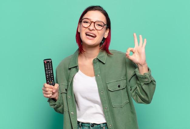 Młoda atrakcyjna kobieta z czerwonymi włosami czuje się szczęśliwa, zrelaksowana i usatysfakcjonowana, pokazując aprobatę w porządku gestem, uśmiechając się i trzymając pilota do telewizora