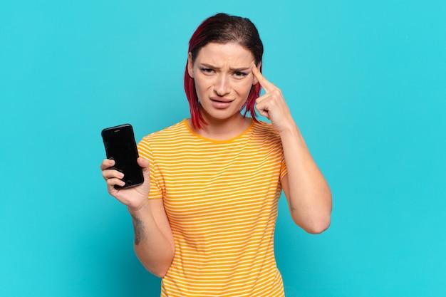 Młoda atrakcyjna kobieta z czerwonymi włosami czuje się zdezorientowana i zdziwiona, pokazując, że jesteś szalony, szalony lub oszalały i pokazując jej komórkę