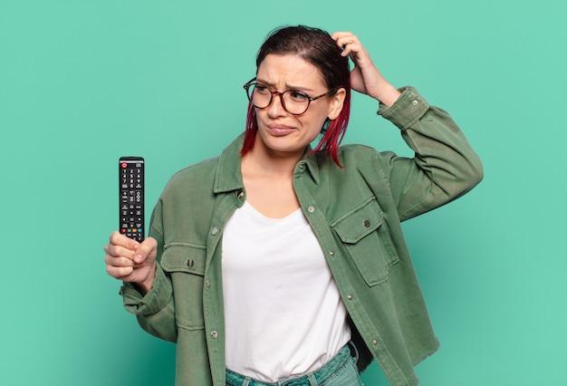 Młoda atrakcyjna kobieta z czerwonymi włosami czuje się zdziwiona i zdezorientowana, drapiąc się po głowie, patrząc w bok i trzymając pilota do telewizora