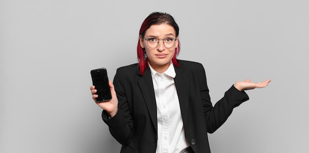 Młoda atrakcyjna kobieta z czerwonymi włosami czuje się zdziwiona i zdezorientowana, wątpi, waży lub wybiera różne opcje z zabawnym wyrazem twarzy. pomysł na biznes