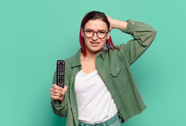 Młoda atrakcyjna kobieta z czerwonymi włosami czuje się zestresowana, zmartwiona, niespokojna lub przestraszona, z rękami na głowie, panikuje podczas pomyłki i trzyma pilota do telewizora