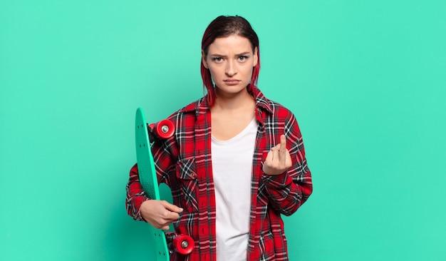 Młoda atrakcyjna kobieta z czerwonymi włosami czuje się zła, zirytowana, zbuntowana i agresywna, macha środkowym palcem, walczy i trzyma deskorolkę