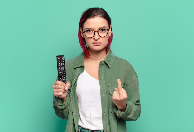 Młoda atrakcyjna kobieta z czerwonymi włosami czuje się zła, zirytowana, zbuntowana i agresywna, macha środkowym palcem, walczy i trzyma pilota do telewizora