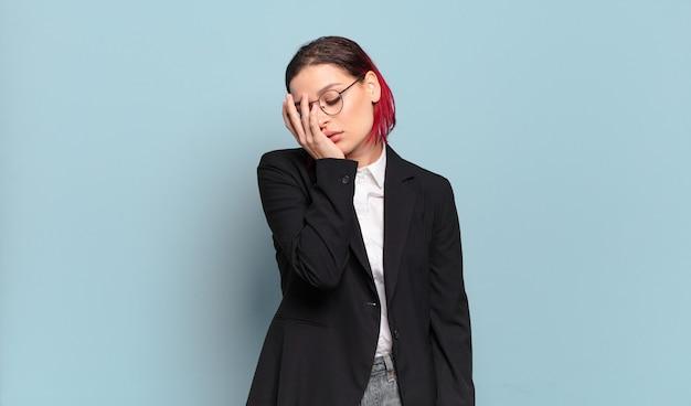 Młoda atrakcyjna kobieta z czerwonymi włosami czuje się znudzona, sfrustrowana i senna po męczącym, nudnym i żmudnym zadaniu, trzymając twarz ręką