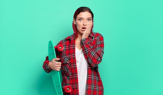 Młoda atrakcyjna kobieta z czerwonymi włosami czuje się zszokowana i przestraszona, wygląda na przerażoną z otwartymi ustami i rękami na policzkach i trzyma deskorolkę
