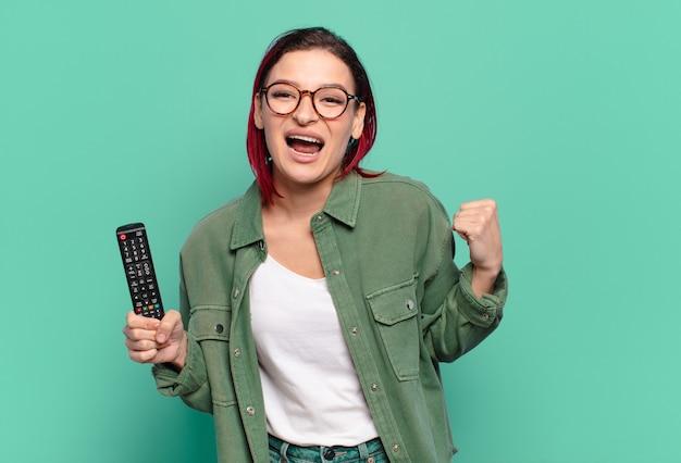 Młoda atrakcyjna kobieta z czerwonymi włosami czuje się zszokowana, podekscytowana i szczęśliwa, śmieje się i świętuje sukces, mówiąc wow! i trzymając pilota do telewizora