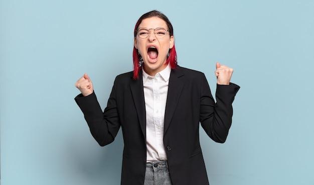 Młoda atrakcyjna kobieta z czerwonymi włosami krzyczy agresywnie z gniewnym wyrazem twarzy lub z zaciśniętymi pięściami świętując sukces