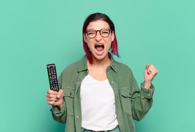 Młoda atrakcyjna kobieta z czerwonymi włosami krzyczy agresywnie ze złym wyrazem twarzy lub z zaciśniętymi pięściami świętuje sukces i trzyma pilota do telewizora