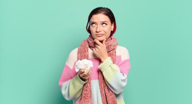Młoda atrakcyjna kobieta z czerwonymi włosami myśli, czuje się niepewna i zdezorientowana, z różnymi opcjami, zastanawiając się, jaką decyzję podjąć koncepcja grypy