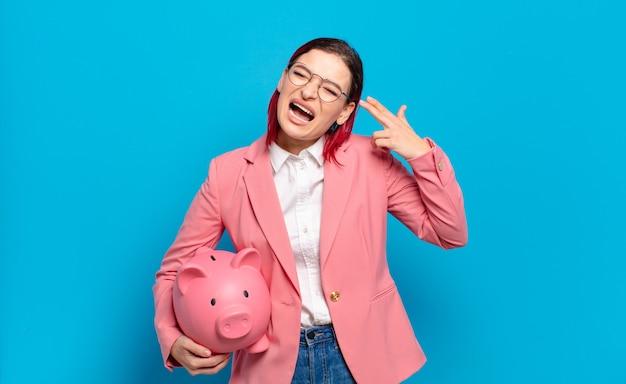 Młoda atrakcyjna kobieta z czerwonymi włosami szuka nieszczęśliwej i zestresowanej, samobójczy gest czyniąc znak pistoletu ręką, wskazując na głowę. humorystyczny pomysł na biznes