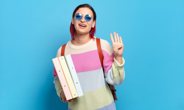 Młoda atrakcyjna kobieta z czerwonymi włosami uśmiecha się i wygląda przyjaźnie, pokazując numer cztery lub czwarte z ręką do przodu, odliczając. koncepcja studenta uniwersytetu