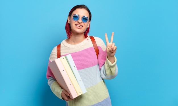Młoda atrakcyjna kobieta z czerwonymi włosami uśmiecha się i wygląda przyjaźnie, pokazując numer dwa lub drugi z ręką do przodu, odliczając. koncepcja studenta uniwersyteckiego