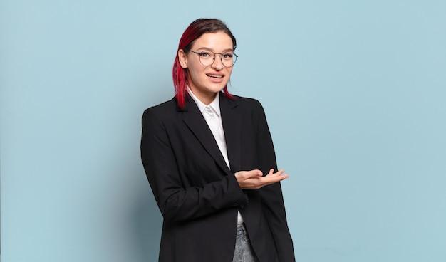 Młoda atrakcyjna kobieta z czerwonymi włosami uśmiecha się radośnie, czuje się szczęśliwa i pokazuje koncepcję w przestrzeni kopii z dłoni