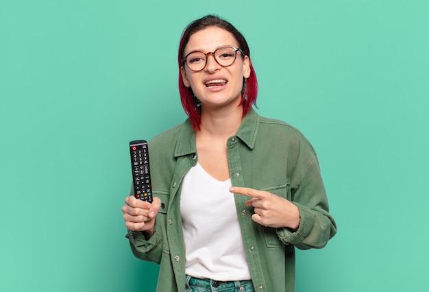 Młoda atrakcyjna kobieta z czerwonymi włosami uśmiecha się radośnie, czuje się szczęśliwa i wskazuje na bok i do góry, pokazuje obiekt w przestrzeni kopii i trzyma pilota do telewizora