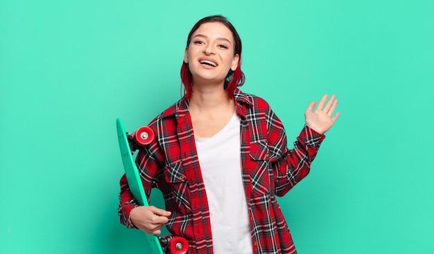 Młoda atrakcyjna kobieta z czerwonymi włosami uśmiecha się radośnie i wesoło, macha ręką, wita i wita lub żegna się i trzyma deskorolkę