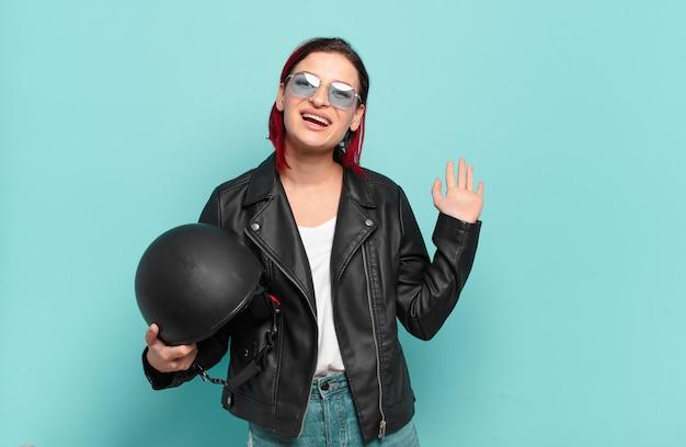 Młoda atrakcyjna kobieta z czerwonymi włosami uśmiecha się radośnie i wesoło, macha ręką, wita i wita lub żegna się. koncepcja motocyklisty