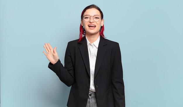 Młoda atrakcyjna kobieta z czerwonymi włosami uśmiecha się radośnie i wesoło, macha ręką, wita i wita lub żegna się