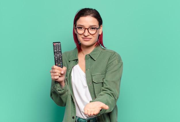 Młoda atrakcyjna kobieta z czerwonymi włosami uśmiecha się radośnie z przyjaznym, pewnym siebie, pozytywnym spojrzeniem, oferuje i pokazuje przedmiot lub koncepcję oraz trzyma pilota do telewizora