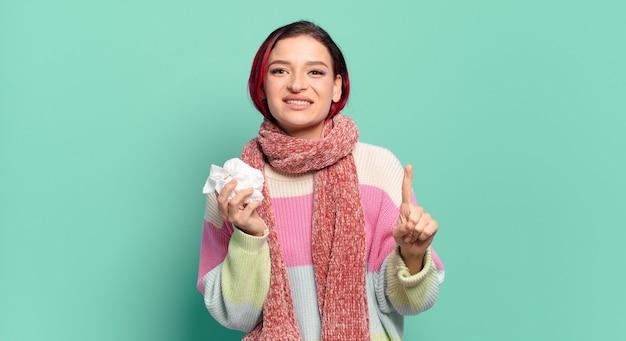 Młoda atrakcyjna kobieta z czerwonymi włosami uśmiechnięta i przyjazna, pokazując numer jeden lub pierwszy ręką do przodu, odliczając pojęcie grypy