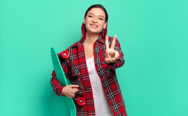 Młoda atrakcyjna kobieta z czerwonymi włosami, uśmiechnięta i wyglądająca na szczęśliwą, beztroską i pozytywną, gestykulującą zwycięstwo lub pokój jedną ręką i trzymającą deskorolkę