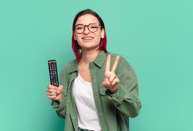 Młoda atrakcyjna kobieta z czerwonymi włosami, uśmiechnięta i wyglądająca na szczęśliwą, beztroską i pozytywną, gestykulującą zwycięstwo lub pokój jedną ręką i trzymającą pilota do telewizora