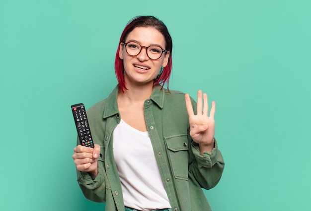 Młoda atrakcyjna kobieta z czerwonymi włosami, uśmiechnięta i wyglądająca przyjaźnie, pokazująca numer cztery lub czwarty z ręką do przodu, odliczająca i trzymająca pilota do telewizora