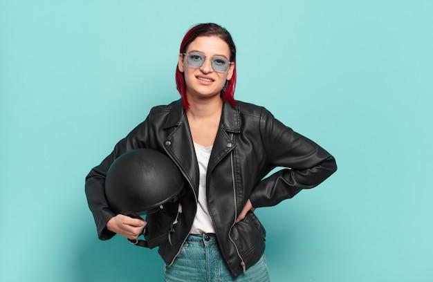 Młoda atrakcyjna kobieta z czerwonymi włosami, uśmiechnięta radośnie z ręką na biodrze i pewną siebie, pozytywną, dumną i przyjazną postawą. koncepcja motocyklisty