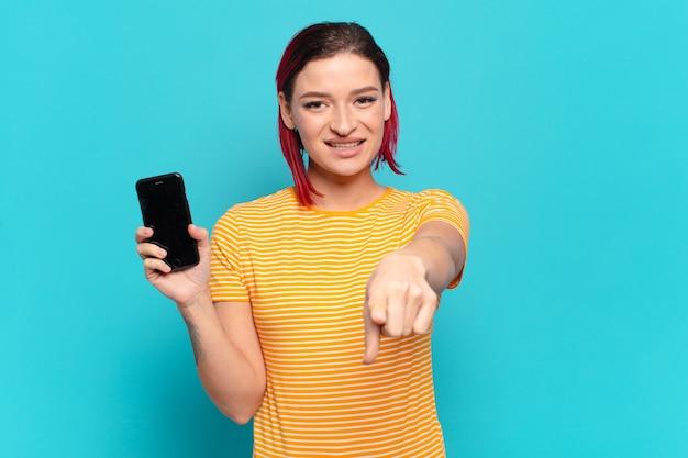 Młoda atrakcyjna kobieta z czerwonymi włosami, wskazując na aparat z zadowolonym, pewnym siebie, przyjaznym uśmiechem, wybierając cię i pokazując jej komórkę