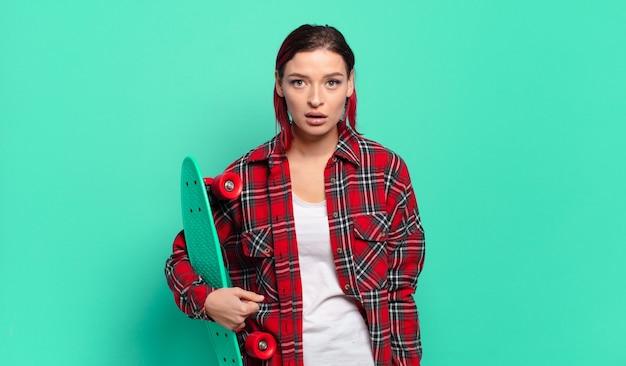 Młoda atrakcyjna kobieta z czerwonymi włosami wygląda na bardzo zszokowaną lub zaskoczoną, patrząc z otwartymi ustami, mówiącą wow i trzymającą deskorolkę