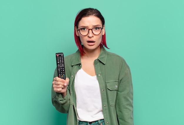 Młoda atrakcyjna kobieta z czerwonymi włosami wygląda na bardzo zszokowaną lub zaskoczoną, patrząc z otwartymi ustami, mówiącą wow i trzymającą pilota do telewizora