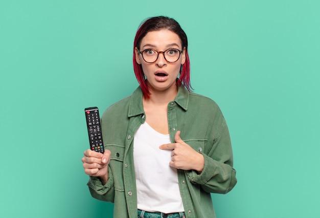 Młoda atrakcyjna kobieta z czerwonymi włosami wygląda na zszokowaną i zaskoczoną z szeroko otwartymi ustami, wskazującą na siebie i trzymającą pilota do telewizora