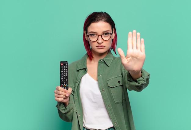 Młoda atrakcyjna kobieta z czerwonymi włosami wygląda poważnie, surowo, niezadowolona i zła, pokazując otwartą dłoń wykonującą gest zatrzymania i trzymającą pilota do telewizora