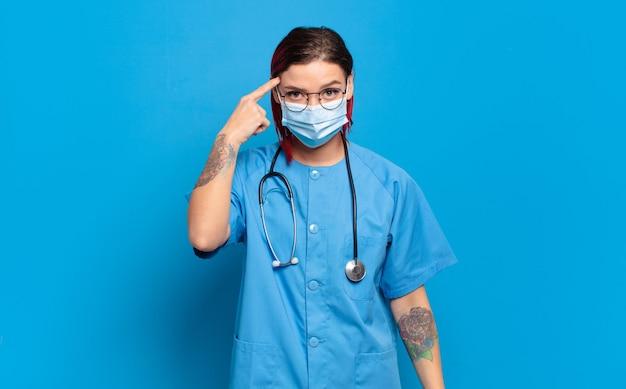 Młoda atrakcyjna kobieta z czerwonymi włosami wygląda zdziwiona, z otwartymi ustami, zszokowana, zdając sobie sprawę z nowej myśli, pomysłu lub koncepcji. koncepcja pielęgniarki szpitalnej