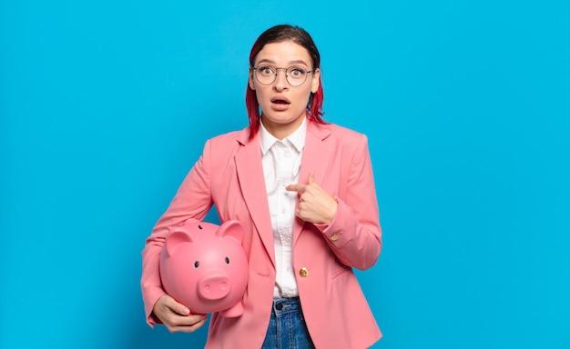 Młoda atrakcyjna kobieta z czerwonymi włosami wygląda zszokowana i zaskoczona z szeroko otwartymi ustami, wskazując na siebie. humorystyczny pomysł na biznes.