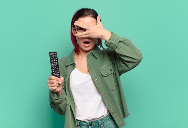 Młoda atrakcyjna kobieta z czerwonymi włosami wygląda zszokowana, przestraszona lub przerażona, trzymając pilota do telewizora