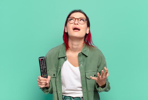 Młoda atrakcyjna kobieta z czerwonymi włosami wyglądająca na zdesperowaną i sfrustrowaną, zestresowaną, nieszczęśliwą i zirytowaną, krzyczącą i krzyczącą oraz trzymającą pilota do telewizora