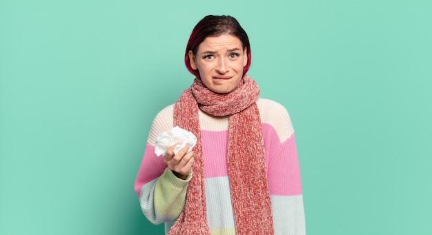 Młoda atrakcyjna kobieta z czerwonymi włosami wyglądająca na zdziwioną i zdezorientowaną, przygryzając wargę nerwowym gestem, nie znając odpowiedzi na problemową koncepcję grypy
