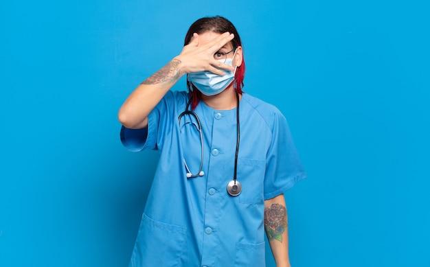 Młoda atrakcyjna kobieta z czerwonymi włosami, wyglądająca na zszokowaną, przestraszoną lub przerażoną, zakrywająca twarz dłonią i zerkająca między palcami. koncepcja pielęgniarki szpitalnej