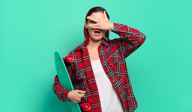 Młoda atrakcyjna kobieta z czerwonymi włosami wyglądająca na zszokowaną, przestraszoną lub przerażoną, zakrywająca twarz ręką i zerkająca między palcami i trzymająca deskorolkę