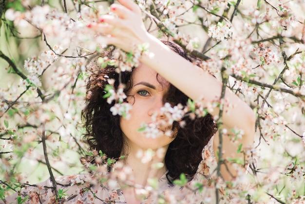 Młoda atrakcyjna kobieta z długimi kręconymi włosami pozowanie w kwitnący ogród wiosną, jabłonie