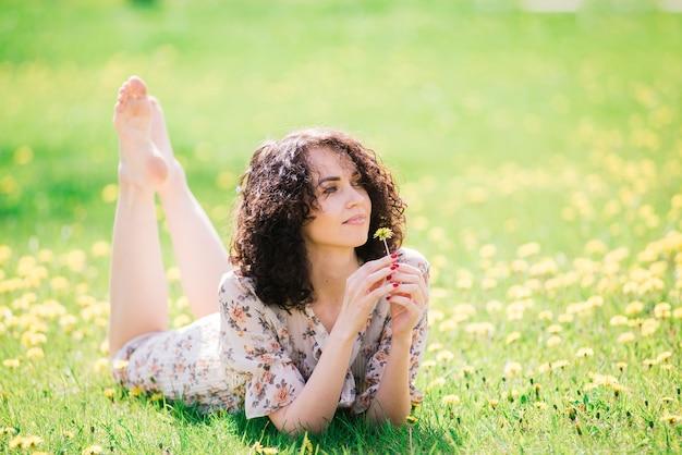 Młoda atrakcyjna kobieta z długimi kręconymi włosami pozowanie w kwitnący ogród wiosną