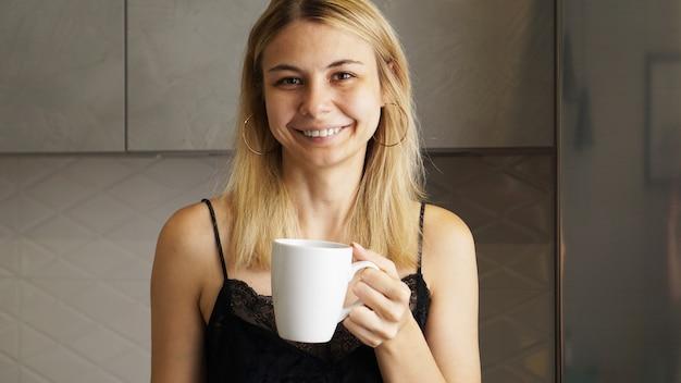 Młoda atrakcyjna kobieta z filiżanką kawy uśmiecha się do kamery