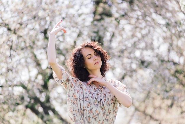 Młoda atrakcyjna kobieta z kędzierzawymi długie włosy pozować w wiosny kwitnienia ogródzie, jabłonie