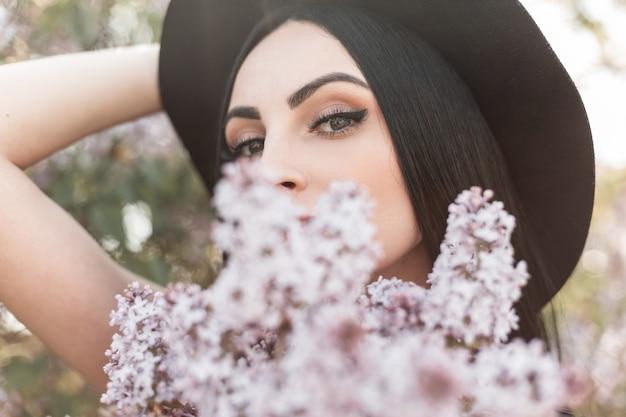 Młoda atrakcyjna kobieta z pięknymi oczami w luksusowy elegancki kapelusz obejmuje twarz bukietem świeżych kwiatów bzu w kwitnącym parku. urocza dziewczyna lubi zapach wiosennych kwiatów i ciepłych wiosennych promieni słońca