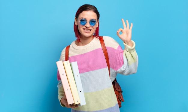 Młoda atrakcyjna kobieta z rudymi włosami czuje się szczęśliwa, zrelaksowana i usatysfakcjonowana, pokazując aprobatę w porządku gestem, uśmiechając się. koncepcja studenta uniwersytetu