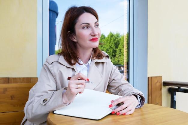 Młoda atrakcyjna kobieta z rudymi włosami siedzi na ulicy przy kawiarnianym stoliku z papierowym notatnikiem i długopisem i patrzy z namysłem w dal. kobieta robi listę rzeczy do zrobienia. kobieta czeka na inspirację.