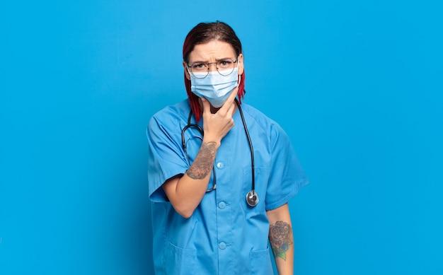 """Młoda atrakcyjna kobieta z rudymi włosami, szeroko otwartymi ustami i oczami, z ręką na brodzie, nieprzyjemnie zszokowana, mówiąca """"co"""" lub """"wow"""". koncepcja pielęgniarki szpitalnej"""