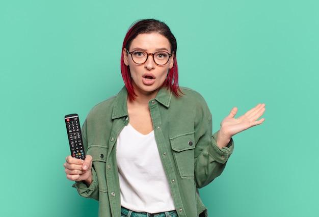 Młoda atrakcyjna kobieta z rudymi włosami wyglądająca na zaskoczoną i zszokowaną, z opuszczoną szczęką, trzymająca przedmiot z otwartą ręką z boku i trzymająca pilota do telewizora