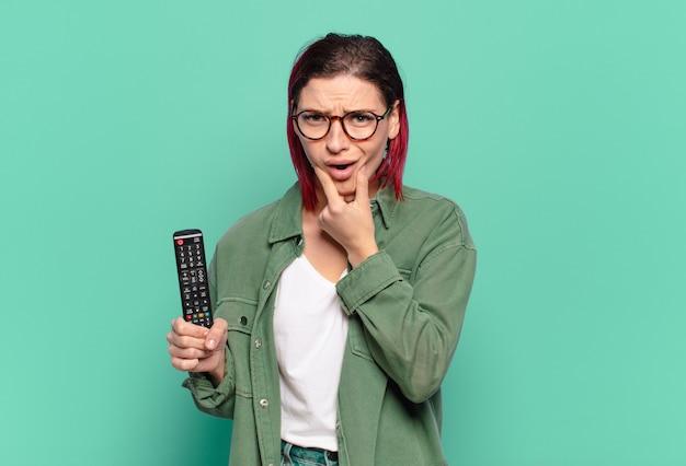 Młoda atrakcyjna kobieta z rudymi włosami z szeroko otwartymi ustami i oczami i ręką na brodzie, czująca się nieprzyjemnie zszokowana, mówiąca co lub wow i trzymająca pilota do telewizora